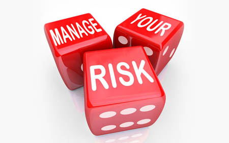 Three red colored dice with white colored words asking to manage your risk