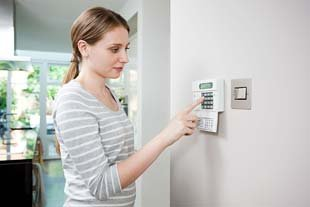 Young lady entering security access code into Access Control system unit on a wall