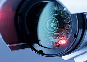 White CCTV Home security camera lens with a red light on