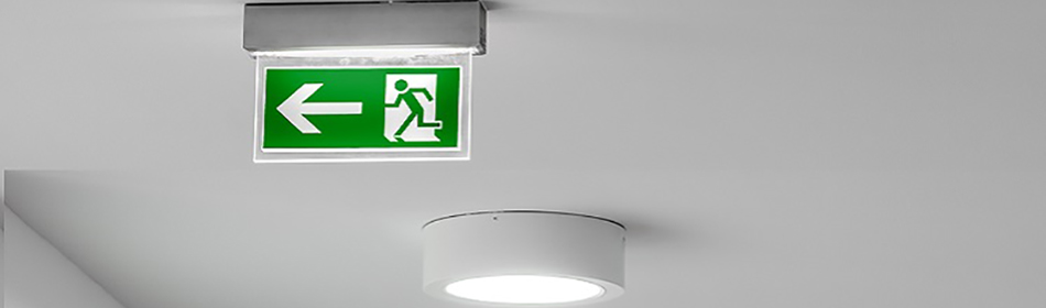 Green and white PVC frame with glass panel emergency exit lighting fitted to the ceiling of commercial premises in Galway